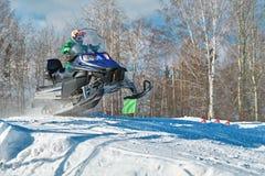 Salto azul de la moto de nieve del deporte Día de invierno soleado con el cielo azul Movimiento rápido del concepto Imagenes de archivo