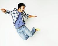 Salto bastante asiático del hombre de los jóvenes alegre contra el fondo blanco Foto de archivo