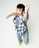 Salto bastante asiático del hombre de los jóvenes alegre contra el fondo blanco, concepto de la gente de la forma de vida Imagen de archivo