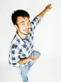 Salto bastante asiático del hombre de los jóvenes alegre contra el fondo blanco, concepto de la gente de la forma de vida Foto de archivo