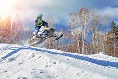 Salto blanco de la moto de nieve del deporte Día de invierno soleado claro Fondo extremo del deporte para cualquier propósitos Mo Fotos de archivo