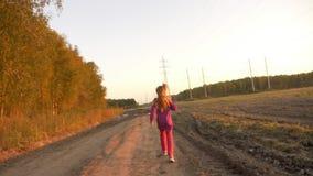 Salto caucásico joven de la muchacha corrido lejos por la carretera nacional sucia Camino del paisaje del otoño y hojas de oro almacen de metraje de vídeo
