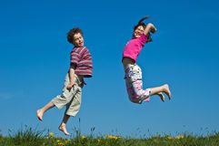 Salto da menina e do menino Imagem de Stock Royalty Free