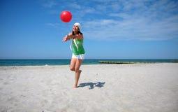 Salto da mulher da esfera de praia fotos de stock royalty free