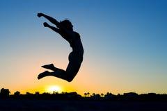 Salto da silhueta da mulher fotografia de stock