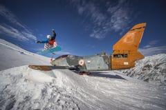 Salto da snowboarding sobre o plano em montanhas do inverno do snowpark Fotos de Stock