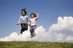 Salto das crianças e do céu fotos de stock