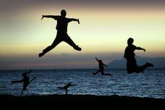 Salto das silhuetas da praia para a alegria fotografia de stock royalty free
