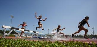 Salto de água das mulheres da trilha da corrida de obstáculos Fotos de Stock