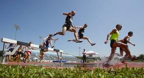 Salto de água dos homens da trilha da corrida de obstáculos Imagem de Stock