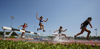 Salto de agua de las mujeres de la pista de la carrera de obstáculos Fotos de archivo