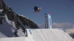Salto de altura del Snowboarder del trampolín Haga el tirón peligroso cameraman asoleado almacen de video