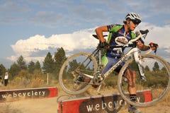 Salto de barrera de Cyclocross Imagen de archivo libre de regalías