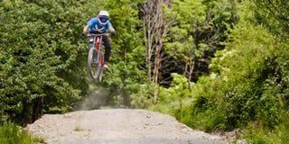 Salto de la bici de Mountainbiker cuesta abajo imagen de archivo libre de regalías