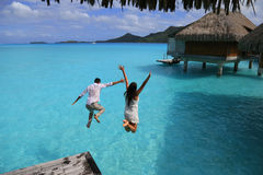 Salto de la felicidad de pares jovenes fotos de archivo