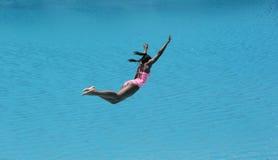 Salto de la muchacha en el agua azul hermosa foto de archivo