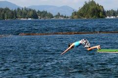 Salto de la muchacha en el lago Fotografía de archivo