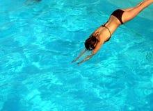 Salto de la muchacha en piscina Fotos de archivo