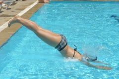 Salto de la muchacha en piscina Imágenes de archivo libres de regalías