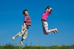 Salto de la muchacha y del muchacho Imagen de archivo libre de regalías
