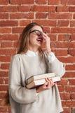 Salto de la mujer joven de risa con los libros Fotografía de archivo libre de regalías
