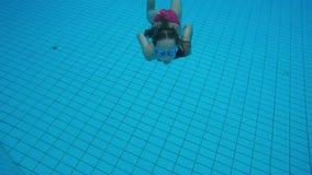 Salto de la niña en piscina y natación a la cámara almacen de metraje de vídeo