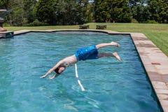 Salto de la piscina del muchacho Foto de archivo libre de regalías