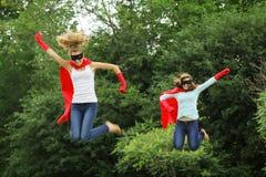 Salto de las personas de los héroes estupendos Foto de archivo libre de regalías