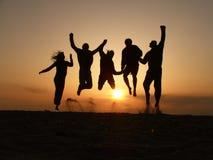 Salto de los amigos de la puesta del sol Imagenes de archivo