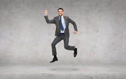 Salto de sorriso do homem de negócios Fotografia de Stock
