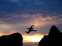 Salto de una sima en puesta del sol Fotos de archivo
