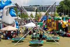 Salto del amortiguador auxiliar de los niños en los trampolines en el festival de artes del verano Fotografía de archivo