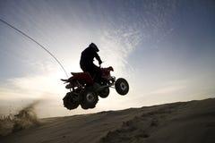 Salto del atv de la duna en la puesta del sol Fotografía de archivo