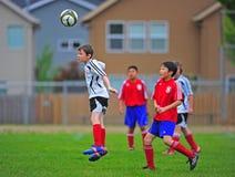 Salto del fútbol de la juventud para una bola principal Imagen de archivo libre de regalías