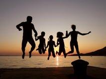 Salto del falò, della madre, del padre e delle figlie Fotografia Stock