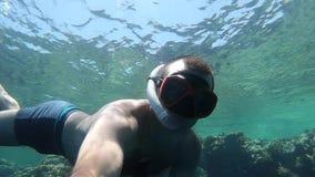 Salto del hombre con la máscara en el Mar Rojo en el fondo de los corales, pescados coloreados almacen de metraje de vídeo