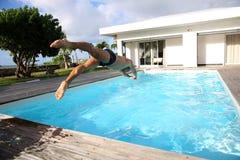 Salto del hombre en piscina Imagen de archivo