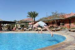 Salto del hombre en una piscina Fotografía de archivo