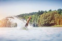 Salto del hombre joven en un lago fotos de archivo