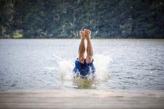 Salto del hombre joven en un lago imagen de archivo libre de regalías