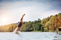 Salto del hombre joven en un lago fotografía de archivo libre de regalías