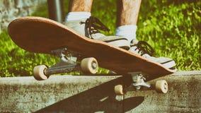Salto del monopatín Skater de Ypung listo para hacer un truco en su tablero Vintage entonado fotos de archivo libres de regalías