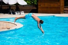 Salto del muchacho en piscina Imagen de archivo libre de regalías