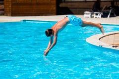 Salto del muchacho en piscina Imágenes de archivo libres de regalías