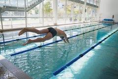Salto del nadador en la piscina en el centro del ocio foto de archivo libre de regalías