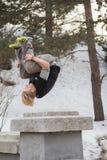 Salto del parkour del entrenamiento del hombre del pelo rubio del adolescente en el parque nevado Fotografía de archivo