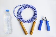 Salto della corda, bottiglia di acqua e polso e strumento della molla di esercizio del muscolo dell'avambraccio isolati su fondo  fotografia stock