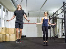 Salto della corda dell'uomo e della donna alla palestra Immagine Stock