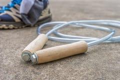 Salto della corda sul pavimento di calcestruzzo con la scarpa dietro fotografia stock