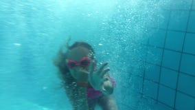 Salto divertido de la muchacha del adolescente en el agua en piscina en hotel del verano metrajes
